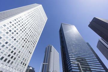 新宿高層ビル街快晴 青空 超広角で見上げる コピースペース ビルに反射する太陽