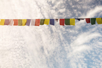 Colorful prayer flags on blue sky background. Nepal or Tibet Travel