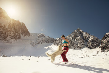 Woman and Dog playing together outdoor in Snow Mountains landscape
