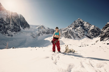 Young Happy Woman doing photo, enjoy and sunbathing in winter mountains with dog