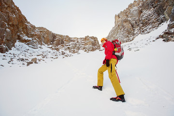 Hiker walking in winter snow high mountains. Extreme Sport outdoor
