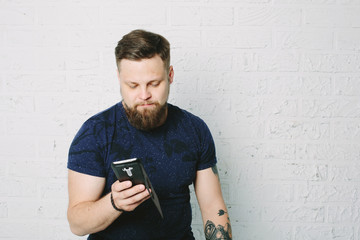 Young hipster man with beard using mobile phone
