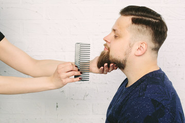 Hipster man in barber shop. Comb for beard. White brick wall background