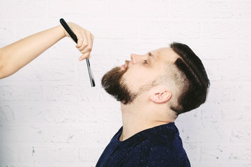 Man in hairstyle salon. hairdresser hands with razor shaving near his face