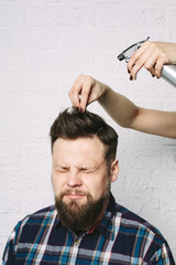 Man with beard in hair salon. hairdresser hands doing hairstyle