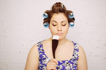 Studio portrait of funny casual woman in big curlers