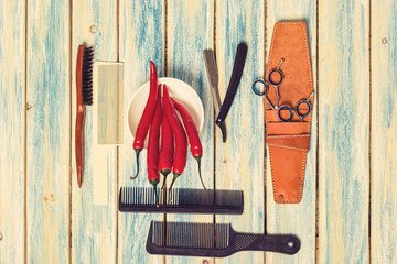 male hairstyle set with red spicy pepper on wooden background: Comb, scissors, razor