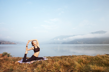 Young Girl doing morning yoga exercise on mountain lake. Fitness sport outdoor