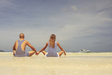 Beautiful happy couple in retro swimsuit relaxing and enjoy on the beach
