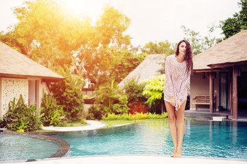 Beautiful girl near swimming pool on luxury villa hotel