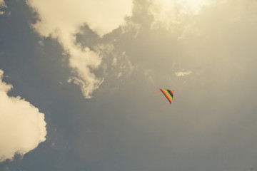 Colorful kite in blue cloud sky