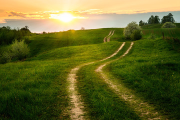 The Sun set over the dirt, winding road. May 2016, Masuria, Poland.