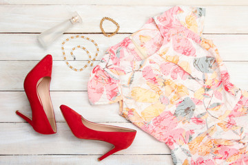 red shoes and dress with the beads with the bracelet and perfume on white wooden background