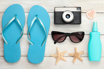 41ff45b778d5 beach shoes with sunglasses and a camera on a white wooden background