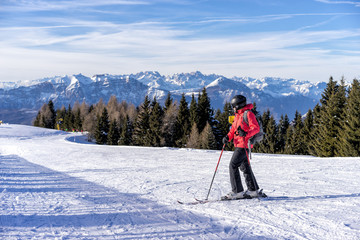 Female skier enjoys view on italien slopes with beautiful mountains in distance.