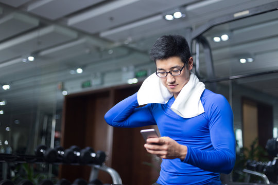 young asian man with smart phone in modern gym