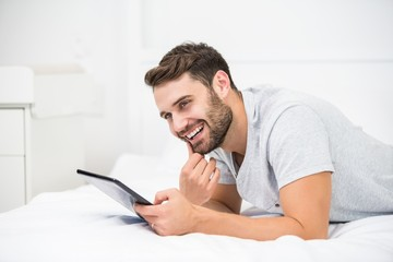Man smiling while using digital tablet on bed