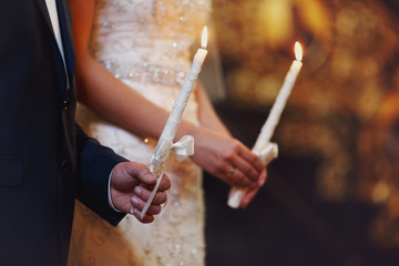 A wedding couple hold in their hands white candles with satin ri