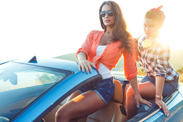Two young happy girls having fun in the cabriolet outdoors