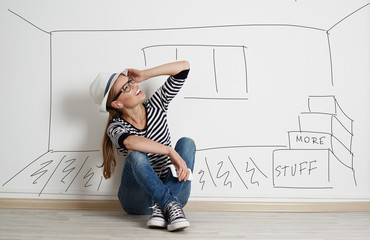 Young optimistic female planning to loan new house sitting at the wall with drawn room. Concept of real estate and ownership.