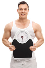 Muscular man holding a weight scale