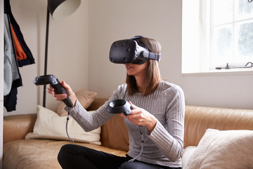 Woman At Home Wearing Virtual Reality Headset Playing Game