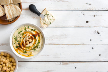Hummus in bowl on white wooden table