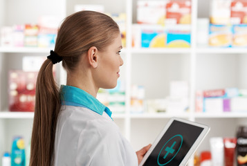 Young woman druggist holding digital tablet pc with cross symbol on the screen. Concept of medical aid and health care.