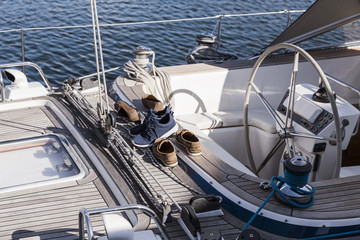 three pairs of shoes in a yacht's wooden deck