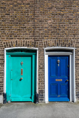Two painted exterior wooden doors next to each other in traditional style, Dublin Ireland.