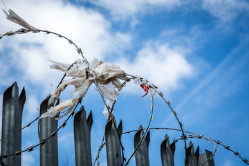 Steel fence with barbed wire with rags, plastic and cloth against blue sky.