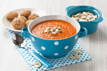 Pumpkin soup / Pumpkin soup with seeds and cookies in blue bowl on wooden background