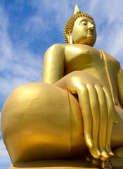Big golden Buddha statues and people in blue sky