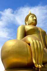 Big golden Buddha statues in blue sky