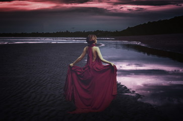woman with dress at the ocean at night