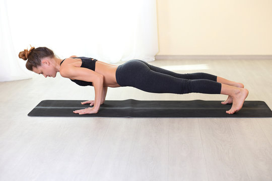 Healthy lifestyle and sports concept. sports and thin woman  exercising. young adult woman doing a plank on yoga mat.