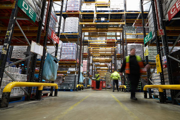 Staff in a warehouse move between storage racks, motion blur