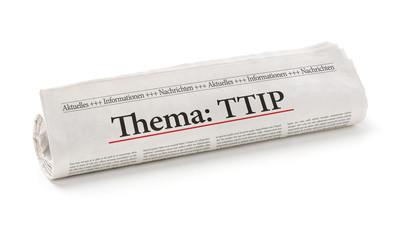 Zeitungsrolle mit der Überschrift Thema TTIP