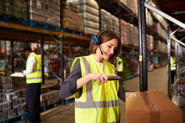 Woman using a barcode reader in a distribution warehouse