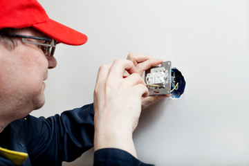 Electrician repairing tumbler switch in the house