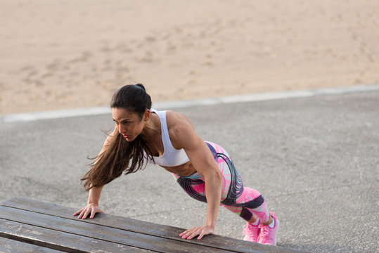 Strong fitness woman doing push ups for chest and arms strength workout. Female muscular motivated athlete training outside.