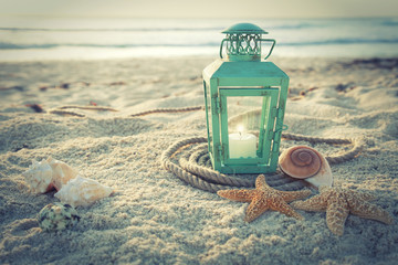 Cross-processed lantern on beach with shells and rope at sunrise
