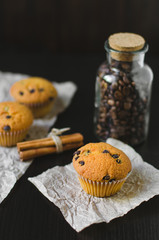 Chocolate muffins with coffee jar and cinnamon on dark background