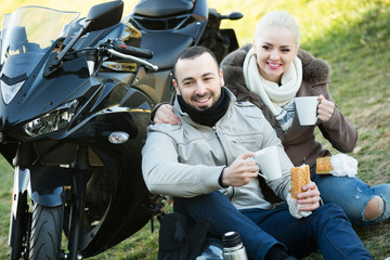 Couple drinking coffee near motorcycle