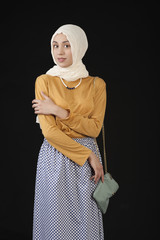 studio photo eastern girl in a headscarf and a modern Islamic Clothes on a dark background