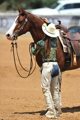 The western style rider with cowboy chaps and hat is caring for her horse