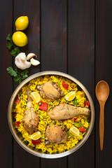 Spanische Paella, traditionelles Reisgericht mit Hähnchen, fotografiert auf dunklem Holz mit natürlichem Licht