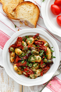Bean salad with addition of dry tomatoes,  olives, capers and fresh parsley in a white bowl