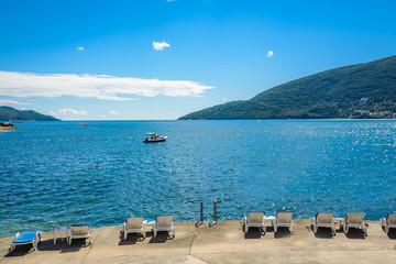Harbor and beach in sunny day at Boka Kotor bay (Boka Kotorska), Montenegro, Europe.