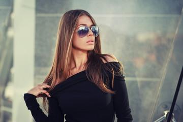 Beautiful brunette young woman in nice black dress, sunglasses. Posing on urban background. Fashion Photo